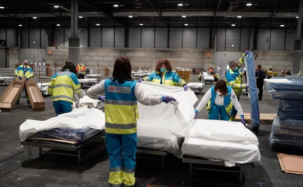 Personal de Emergencias montan las camas en la Feria de Madrid.