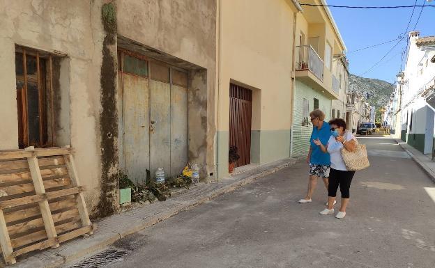Dos vecinos contemplan las barreras de vegetación puestas en una puerta para evitar que los gatos se cuelen en una vivienda.