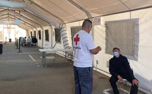Un miembro de Cruz Roja atiende a una de las personas que iba a bordo de la patera interceptada ayer. /E. P.