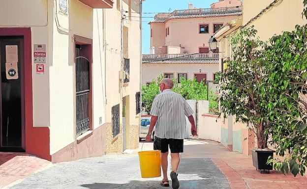 Un vecino camina por la calle donde se encuentra el Ayuntamiento de Bolulla./BO