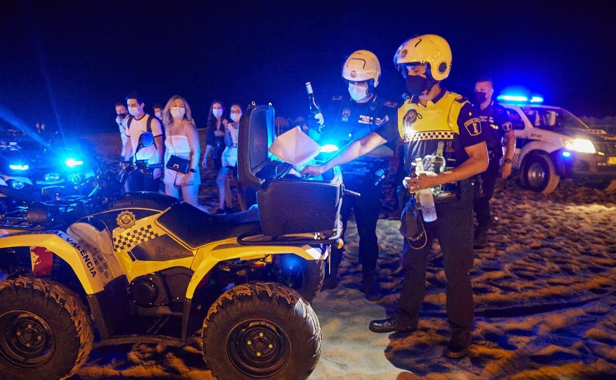 La policía actúa en un botellón en la playa de Valencia./ iván arlandis