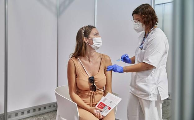 Trabajadores sanitarios administran la vacuna a una joven de la Ciudad de las Artes y las Ciencias de Valencia./iván arlandis